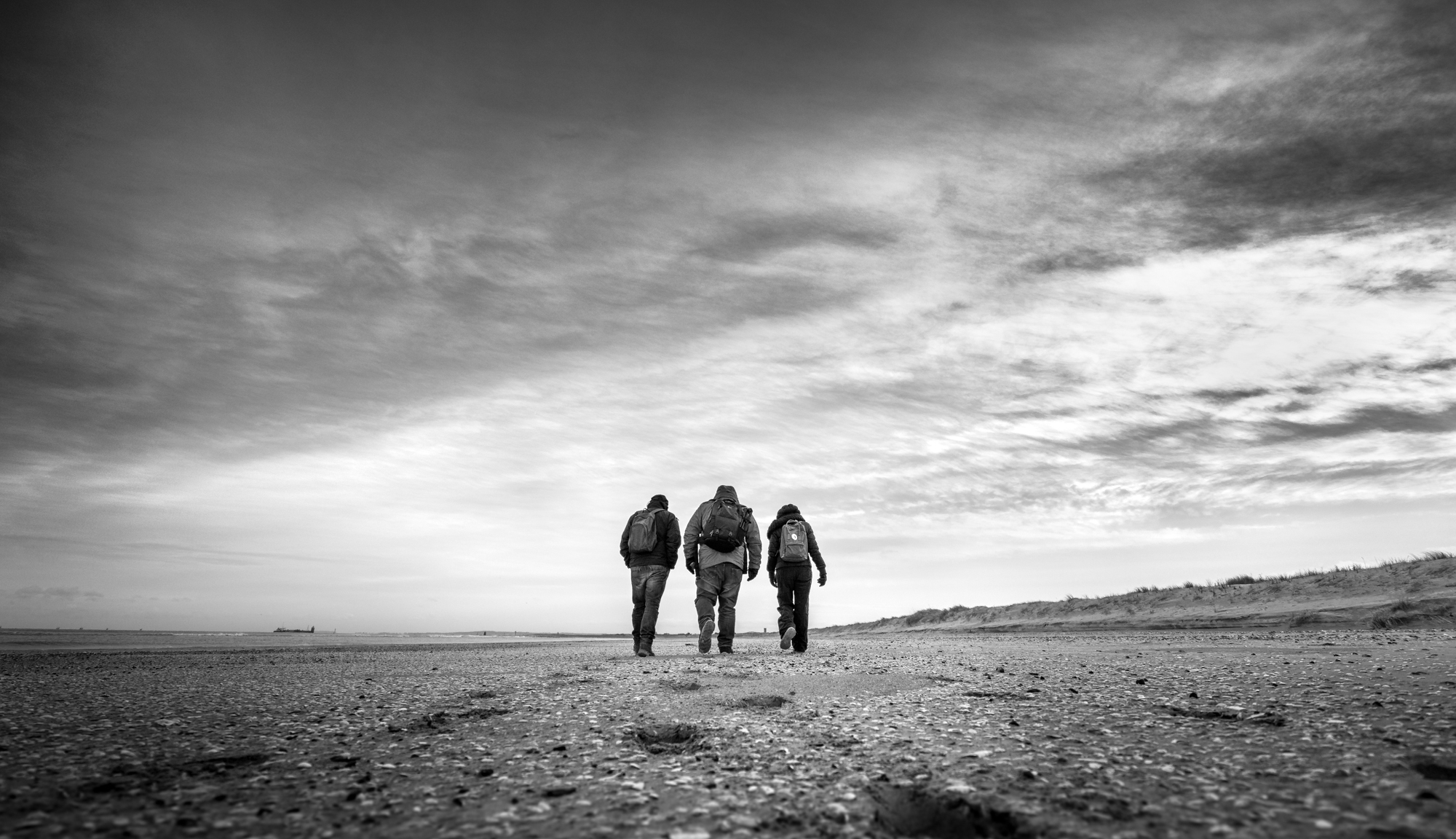 3 people with backpacks walking towards horizon