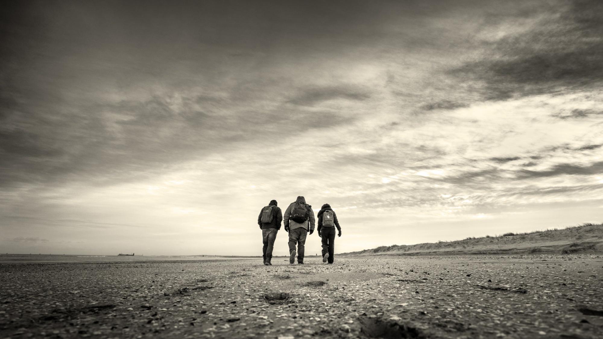 three people with backpacks walking towards horizon