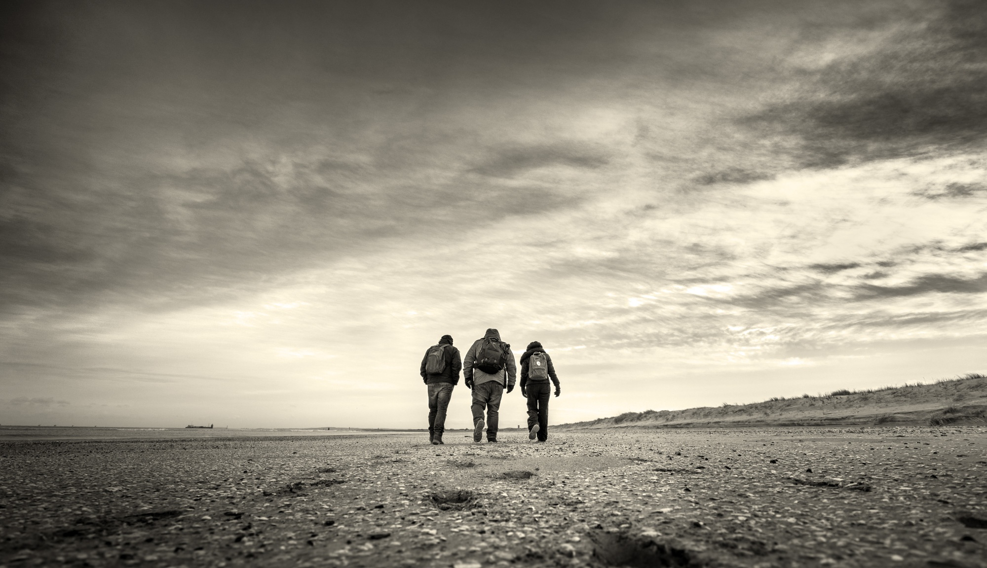 three people with backpacks walking towards horizon