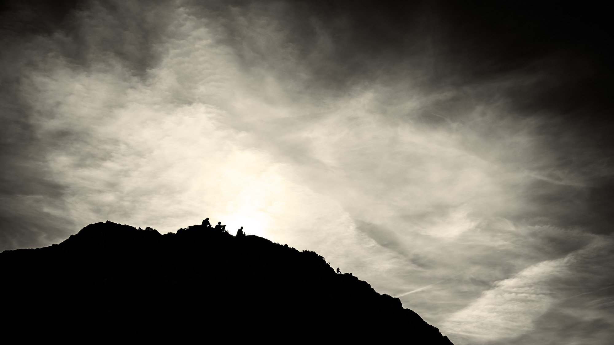 silhouettes of three people sitting on hill